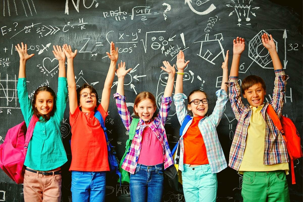 5 kids standing with backpacks on in front of a chalkboard with their hands raised, ready to go back to school.