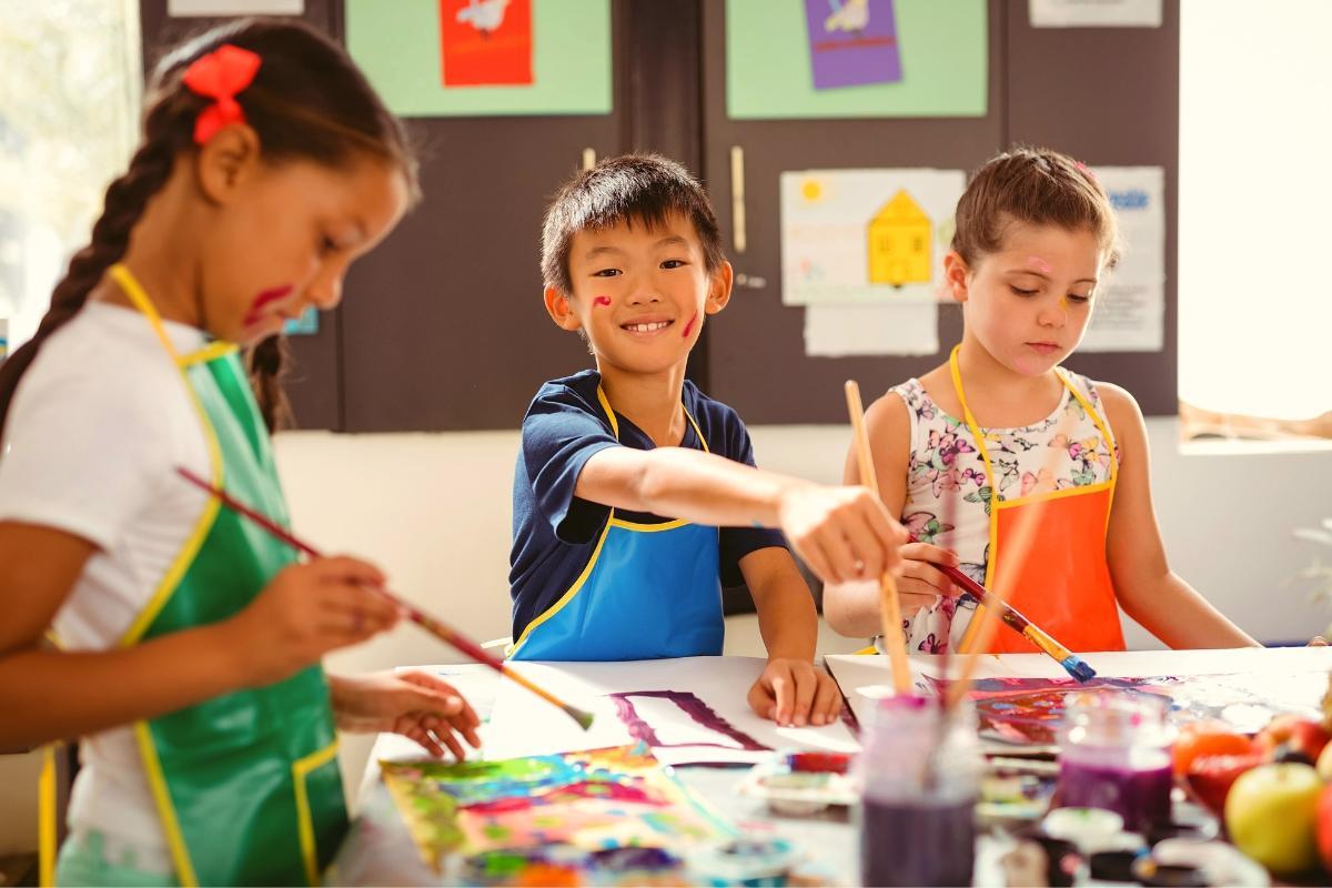 Three kids painting.
