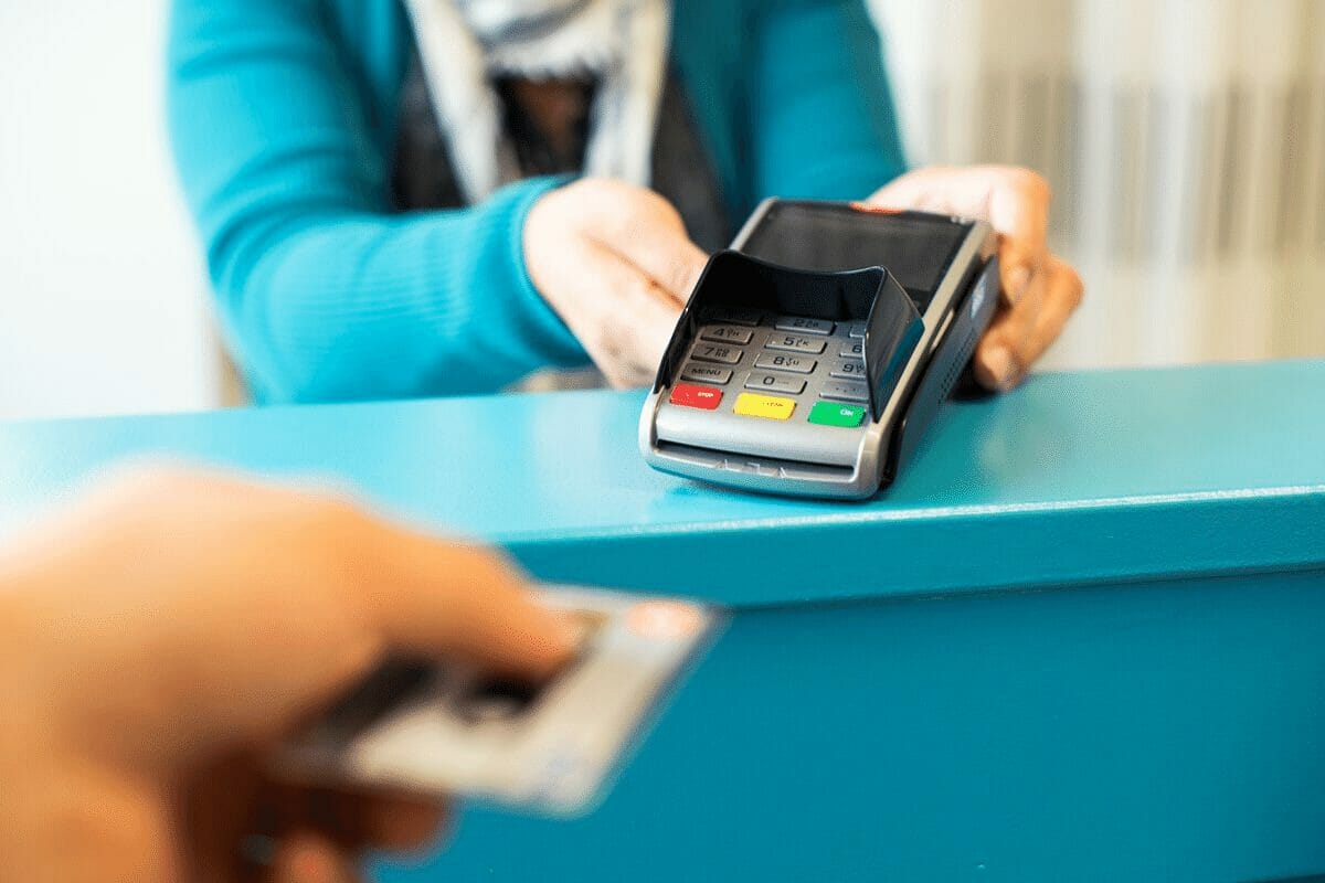 Credit card being put into a payment machine.