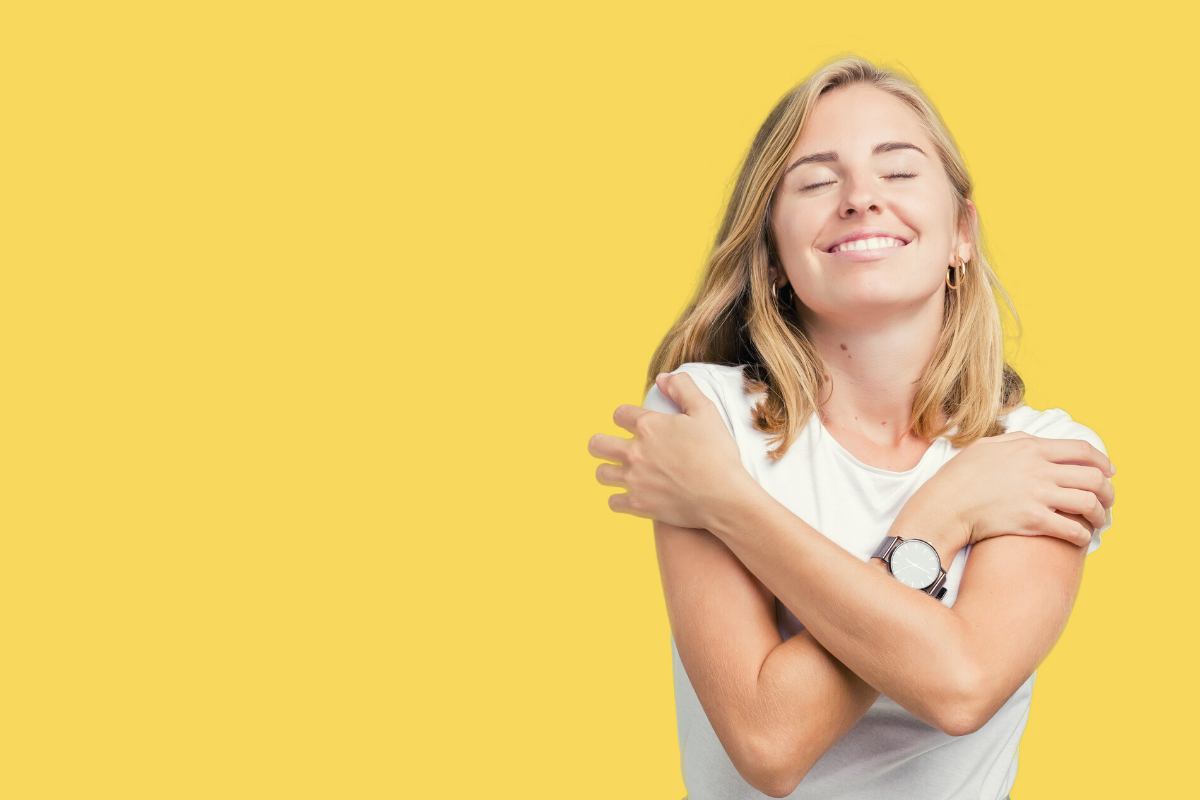 Woman smiling and hugging herself, symbolizing self-care.