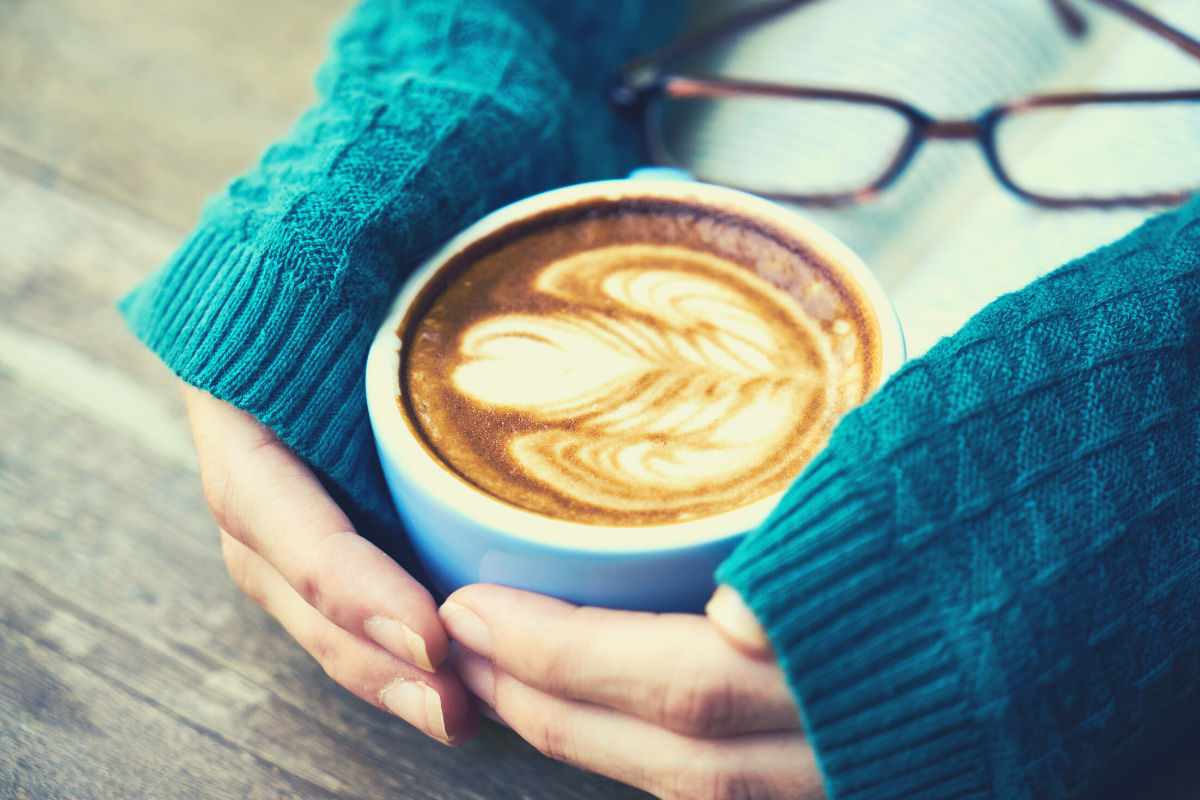 Woman relaxing and holding a coffee cup with coffee in it, relaxing and reading a book.