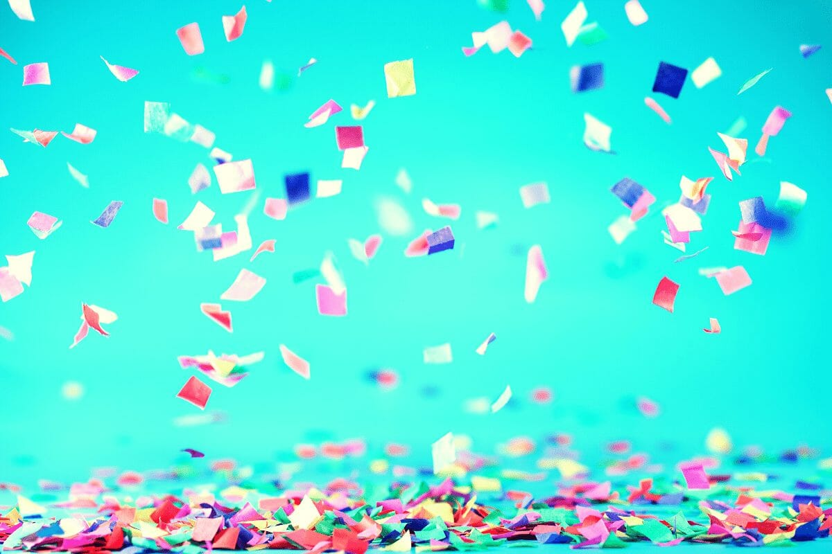 Colorful confetti falling agains a blue background.