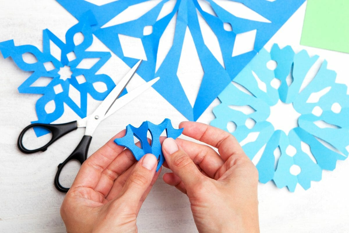 Person cutting out snowflakes from paper.